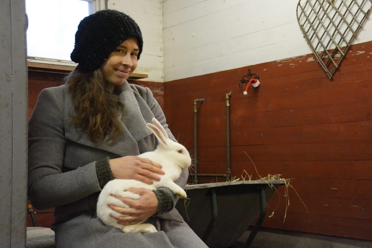 Liisa Koivisto istuu kani sylissään.