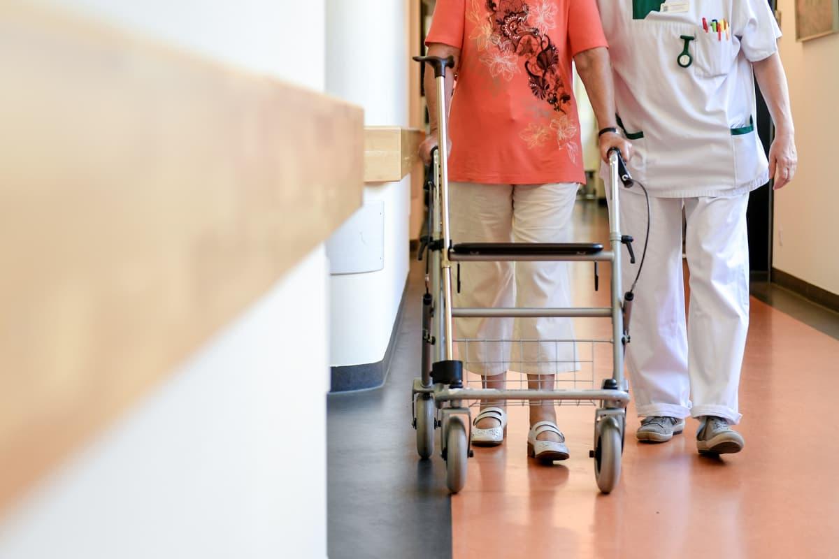 Hoitaja kävelyllä vanhuksen kanssa.