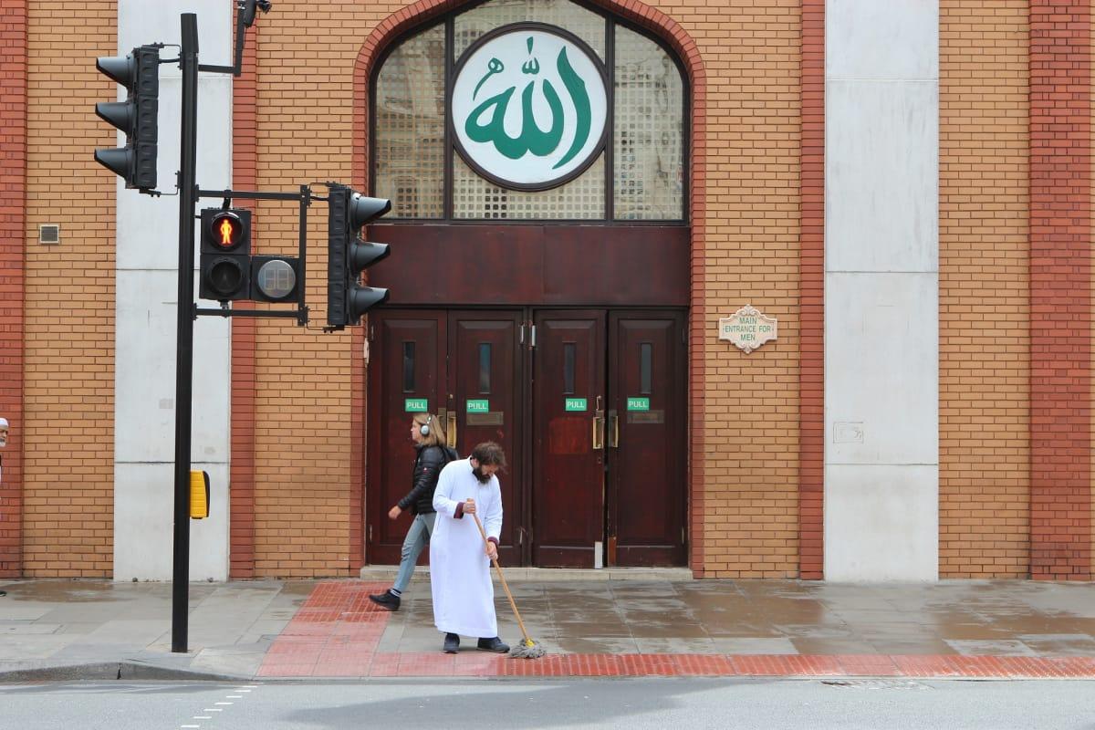 Valkoiseen asuun pukeutunut mies lakaisee katua moskeijan pääoven ja tiilestä rakennetun julkisivun edessä.