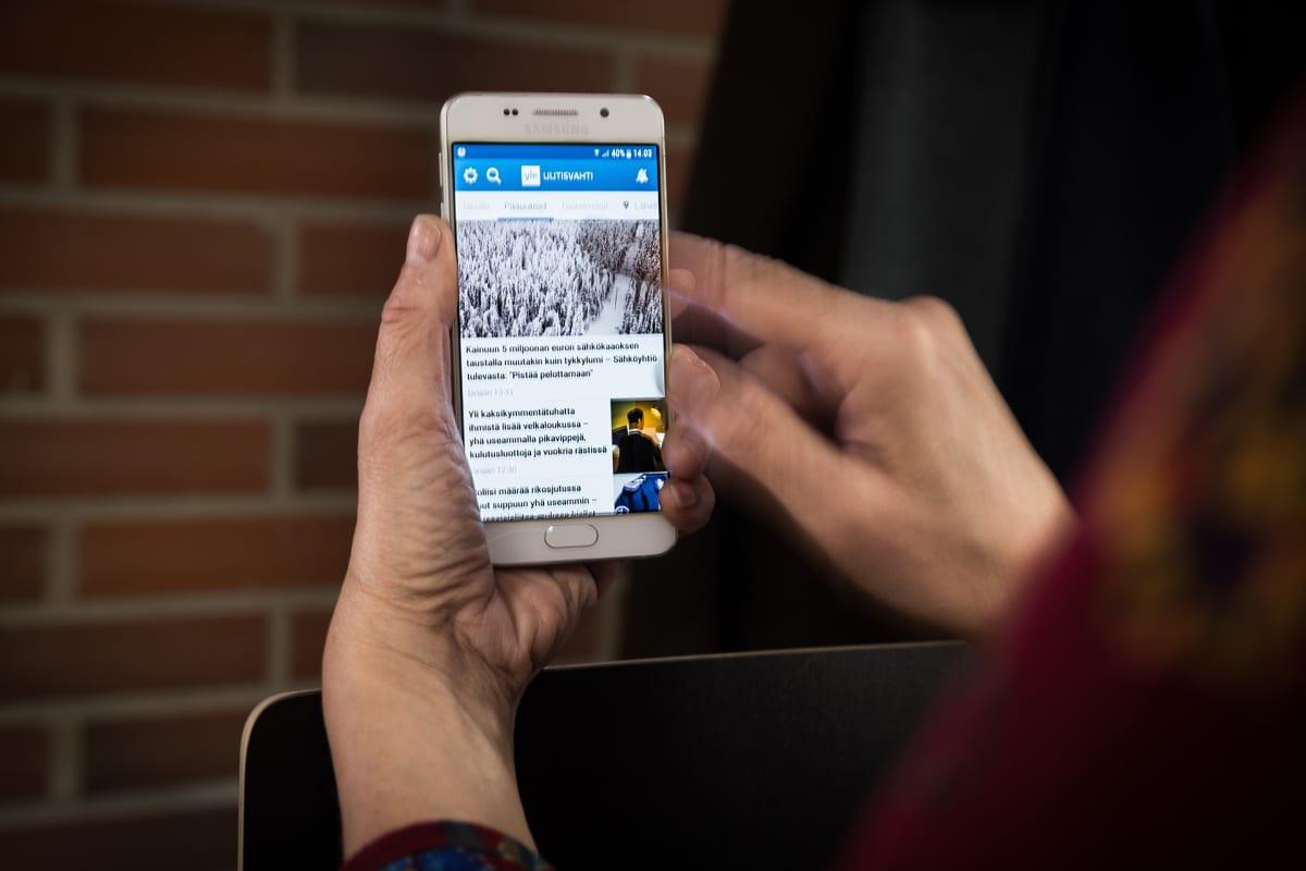 Nainen selaa puhelimella uutisia Ylen uutisaplikaatiolla.
