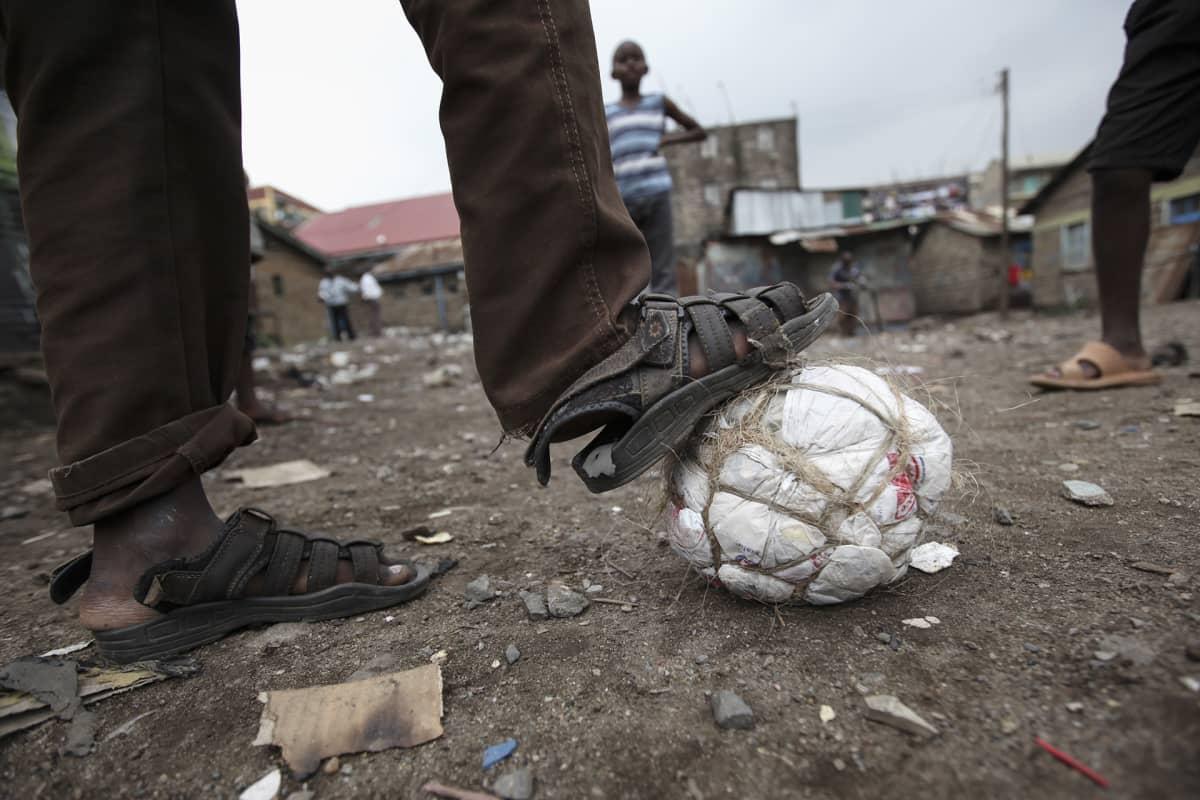 Pojat pelaavat itsetehdyllä jalkapallolla.