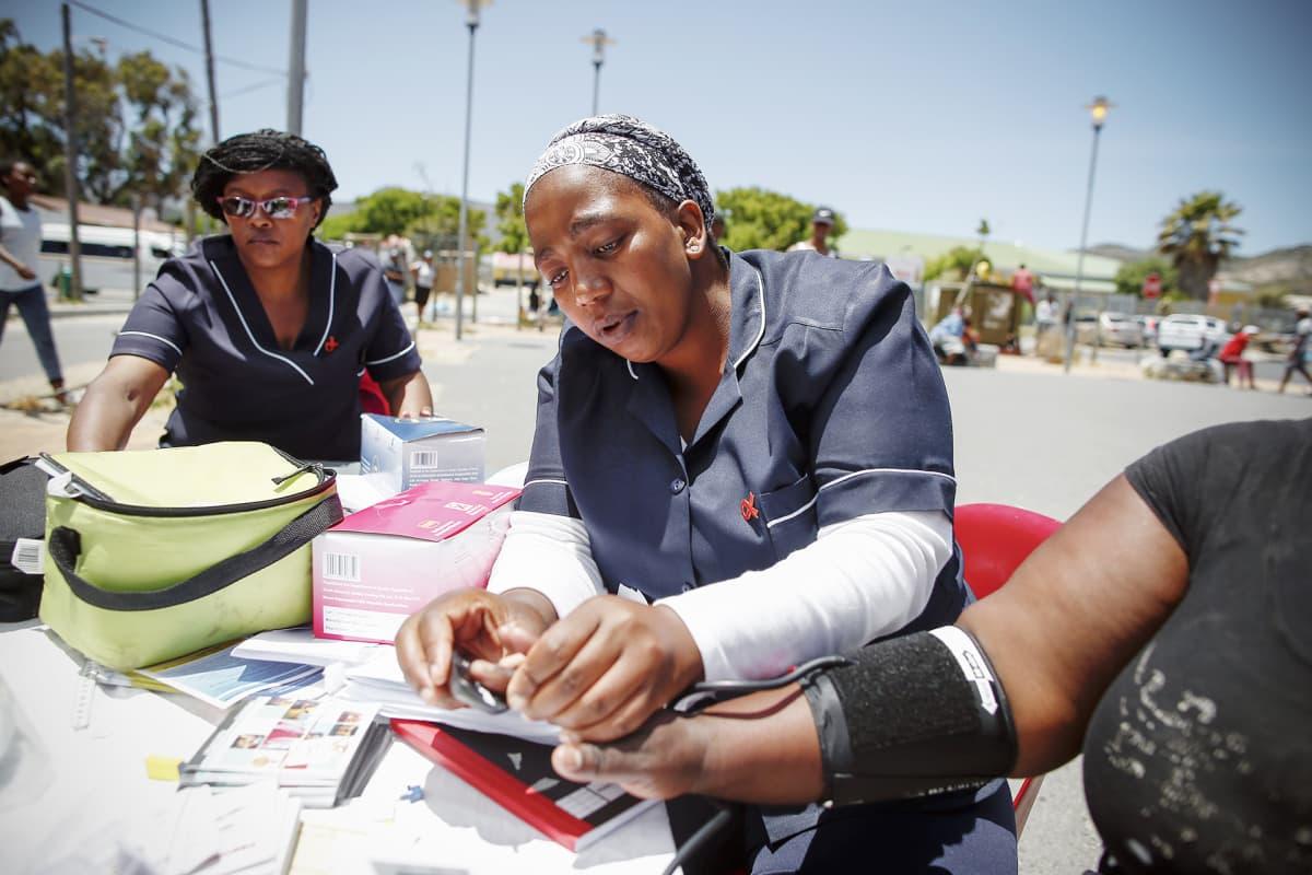 Eteläafrikkalainen sairaanhoitaja jakaa tietoa aidsista sekä mittaa asiakkaiden verenpainetta ja verensokeritasoja Kapkaupungissa.