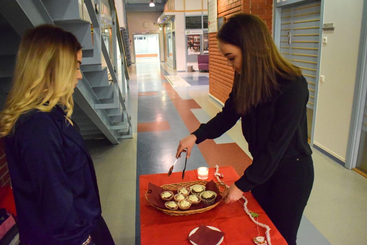 Etelä-Savon ammattiopiston merkonomiopiskelijat Henna Kamppi ja Vilma Leinonen ja leivonnaisia.