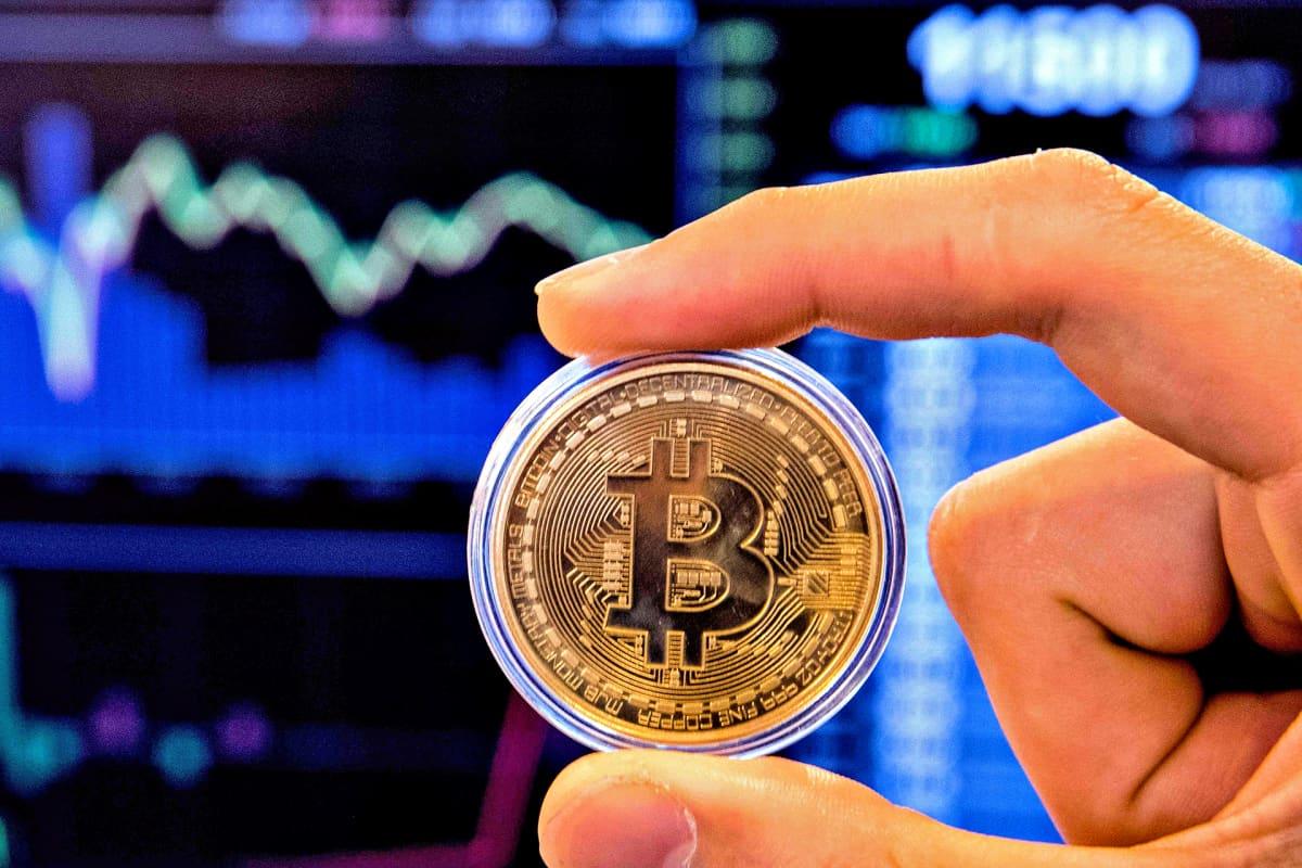 Käsi pitelee Bitcoin-kolikkoa. Takana näkyy alas kaartuva pörssikäyrä.