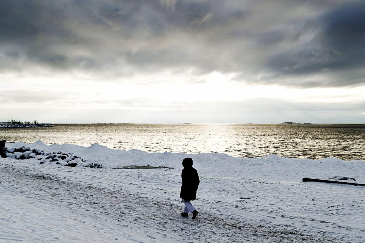 Ulkoilija talvisäässä Helsingin Merisatamanrannassa  maanantaina 22. tammikuuta.