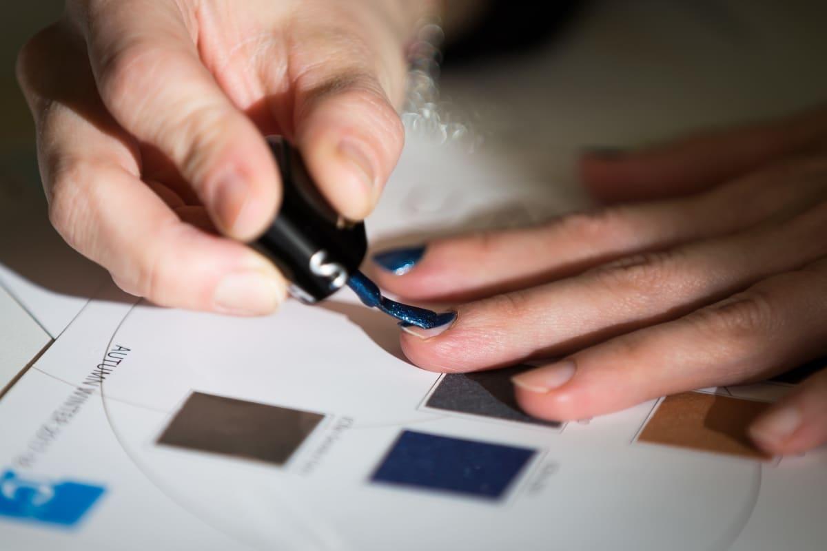 Nainen laittaa tummansinistä kynsilakkaa.