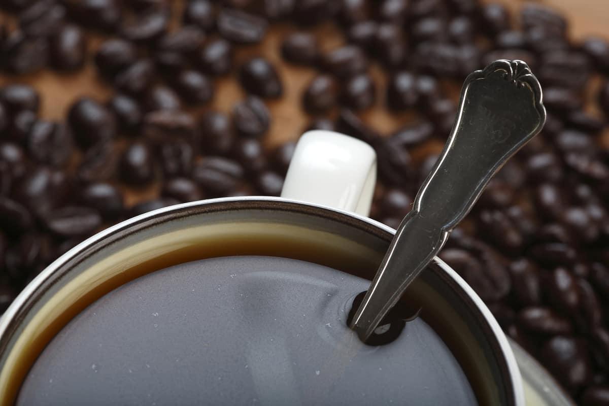 Kahvikuppi ja kahvipapuja.