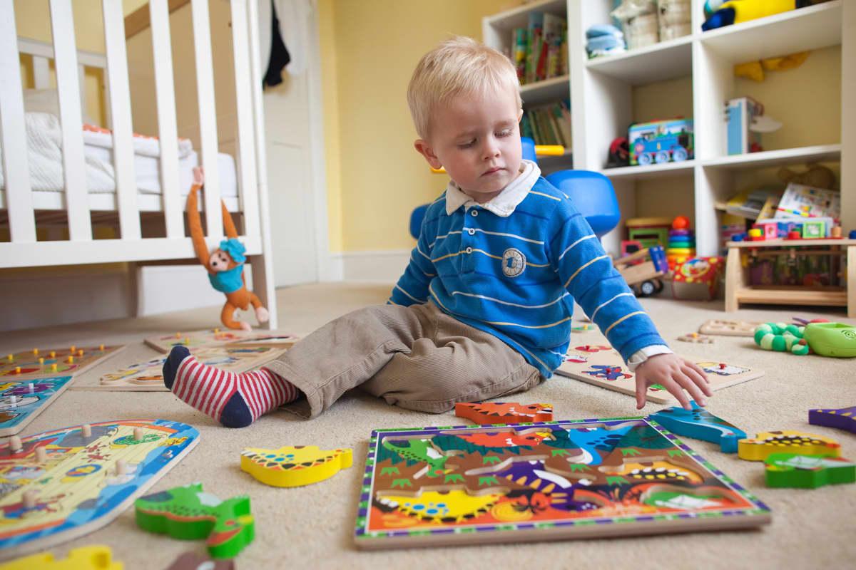 Pieni poika leikkii lattialla.
