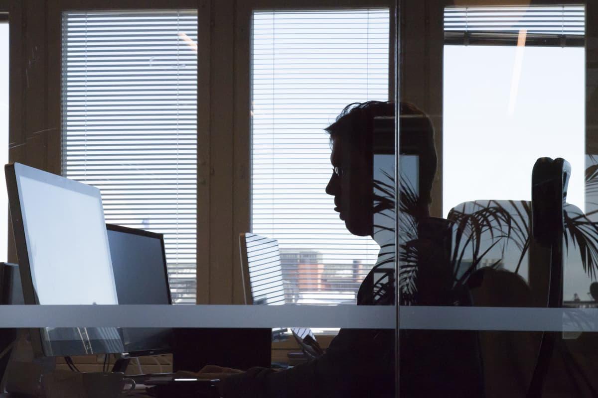 Siluettikuva miehestä tietokoneen ääressä..
