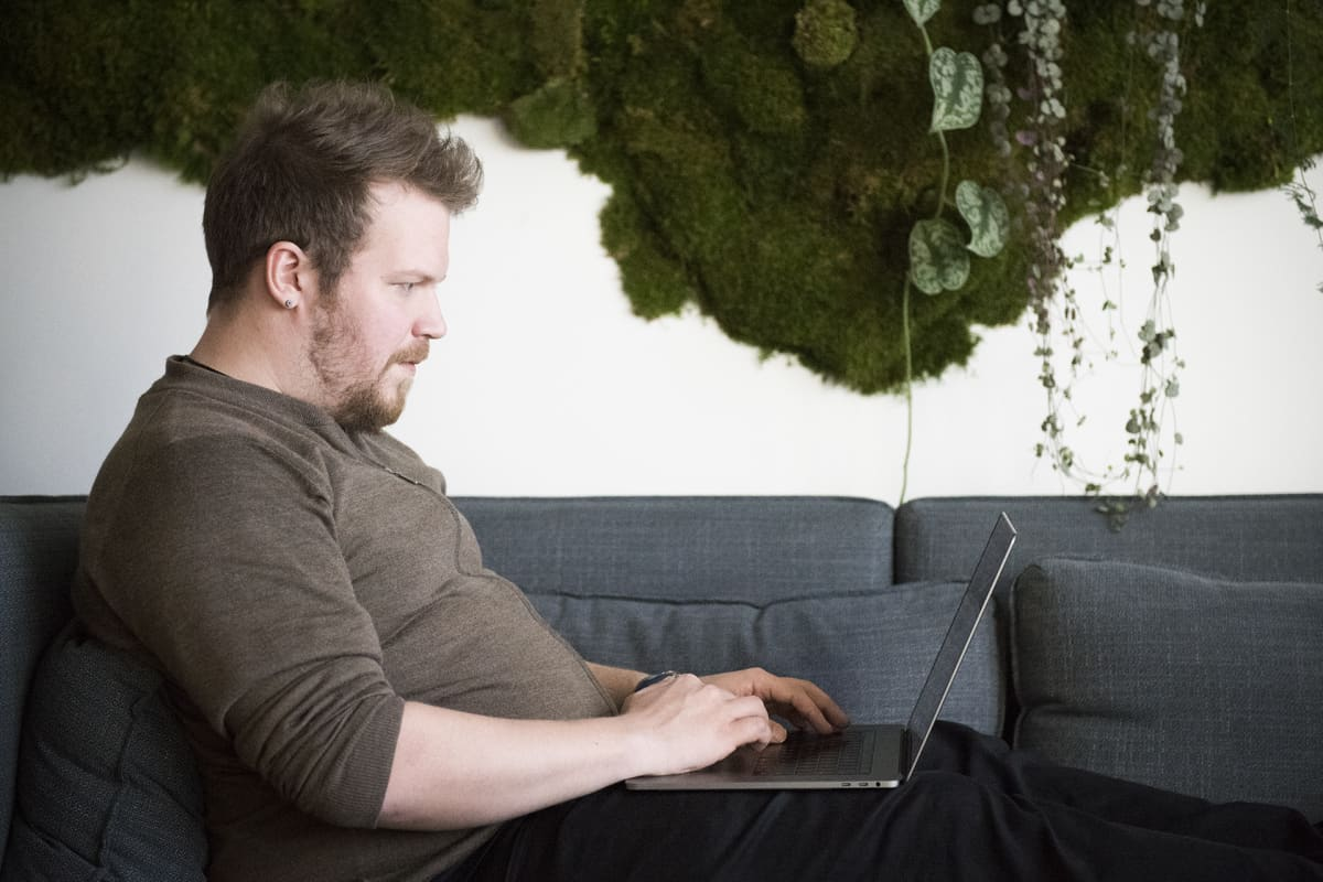 Mies istuu sohvalla läppärin kanssa