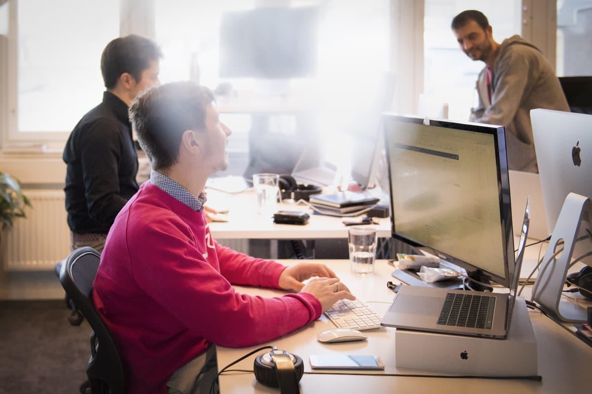 Kolme miestä tietokoneiden ääressä toimistolla.