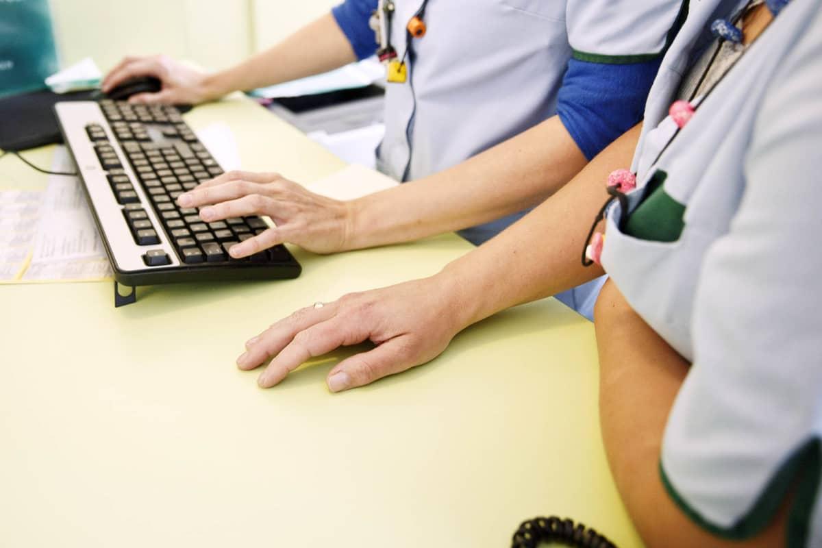 Sairaanhoitajat käyttävät tietokonetta.