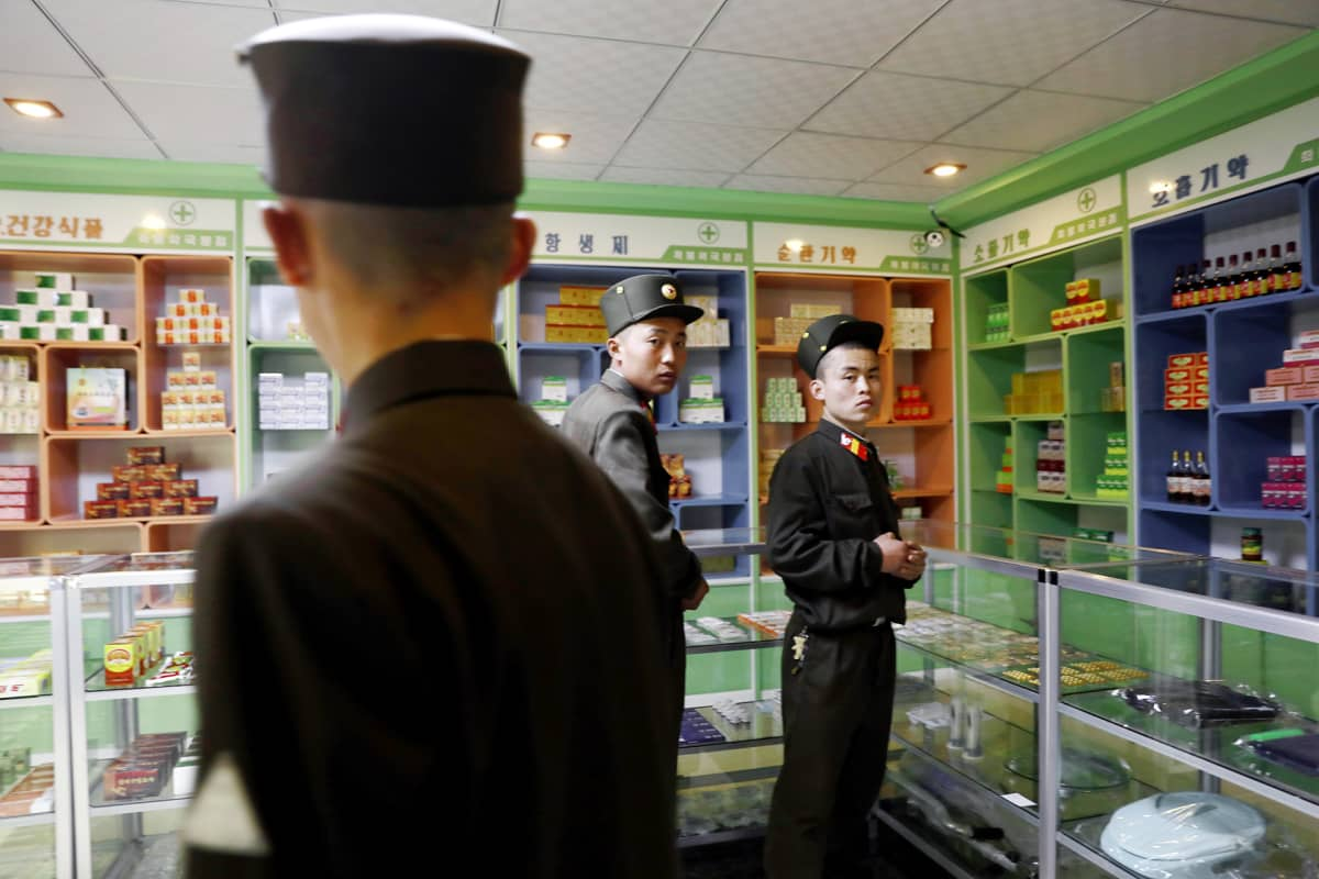 Sotilaat katsovat tuotteita pohjoiskorealaisessa apteekissa Pyongyangissa.