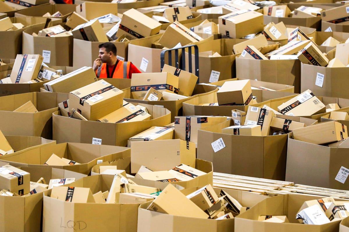 Työntekijä seisoo satojen erikokoiseten pahvilaatikoiden keskellä Amazon -verkkokaupan jakelukeskuksessa.