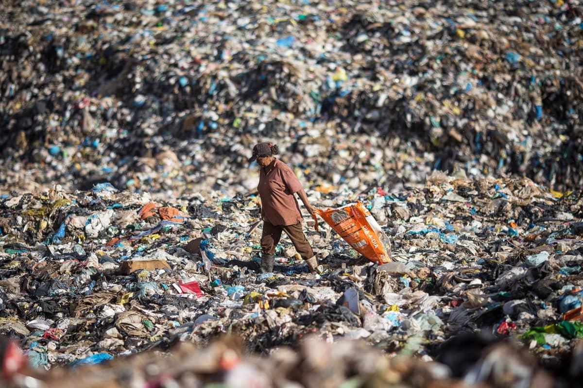 Nainen etsii jätteiden seasta kierrätettäväksi kelpaavia materiaaleja Brasiliassa sijaitsevalla Etelä-Amerikan suurimmalla kaatopaikalla.