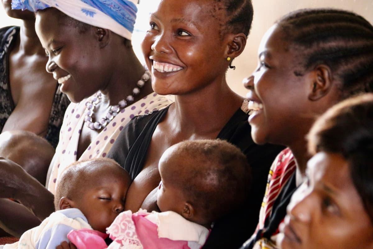 Hymyilevä naine lapsiensa kanssa perhesuunnitteluklinikalla.