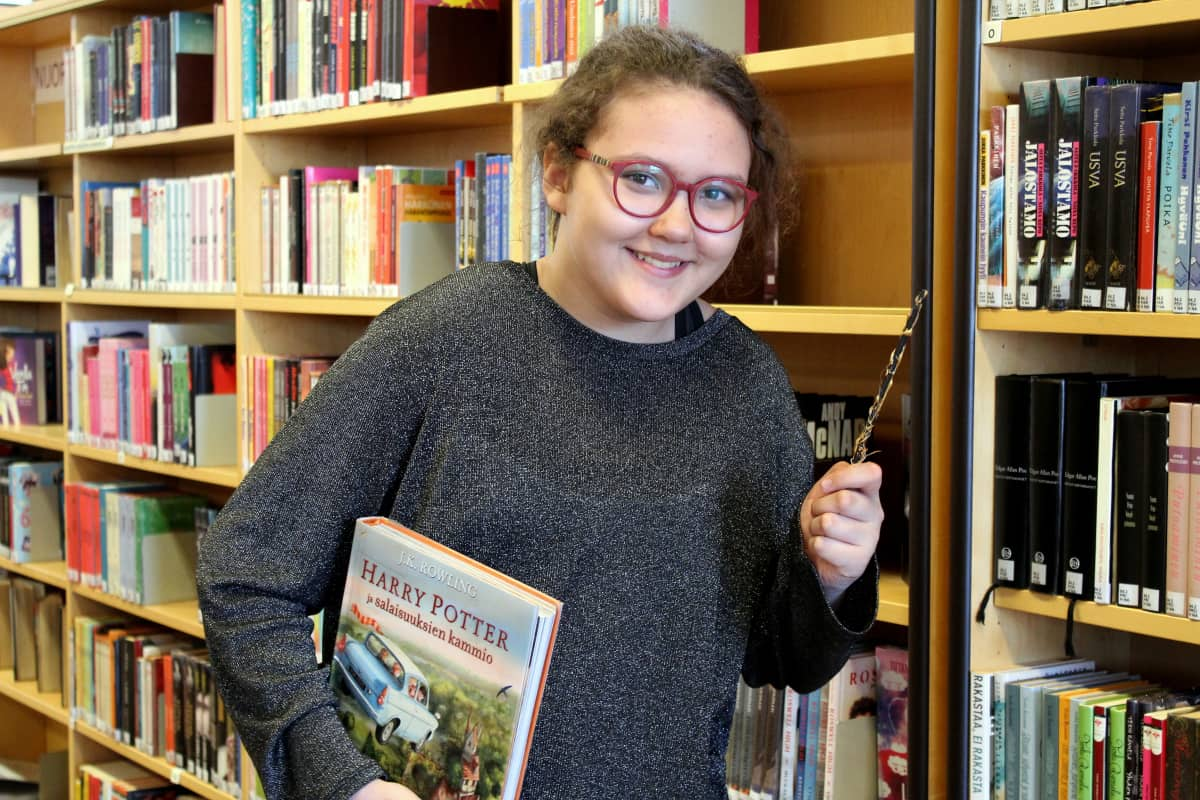 Aida Kankaanpää kirjastossa taikasauva kädessään ja Harry Potter -kirja kainalossaan.