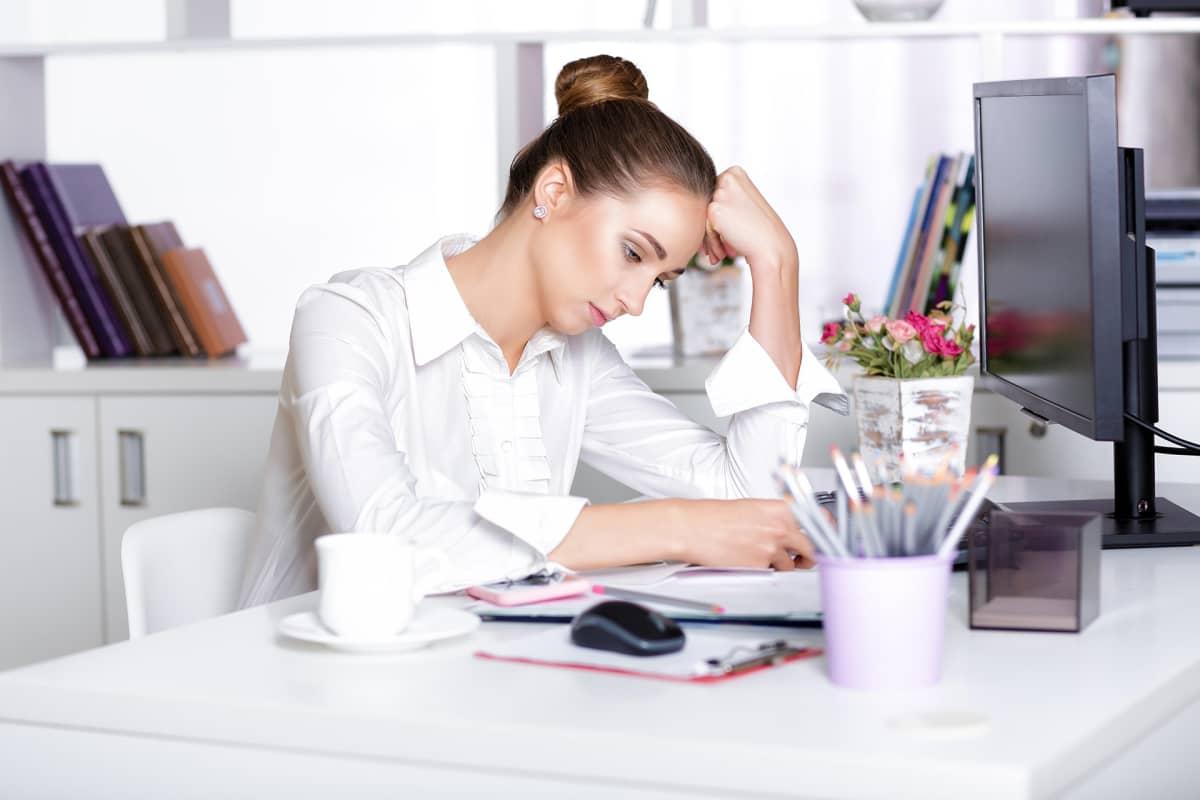 Väsynyt nainen töissä työpöydän äärellä.