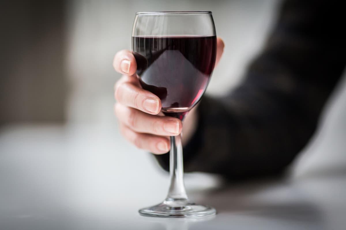 Viinilasi naisen kädessä