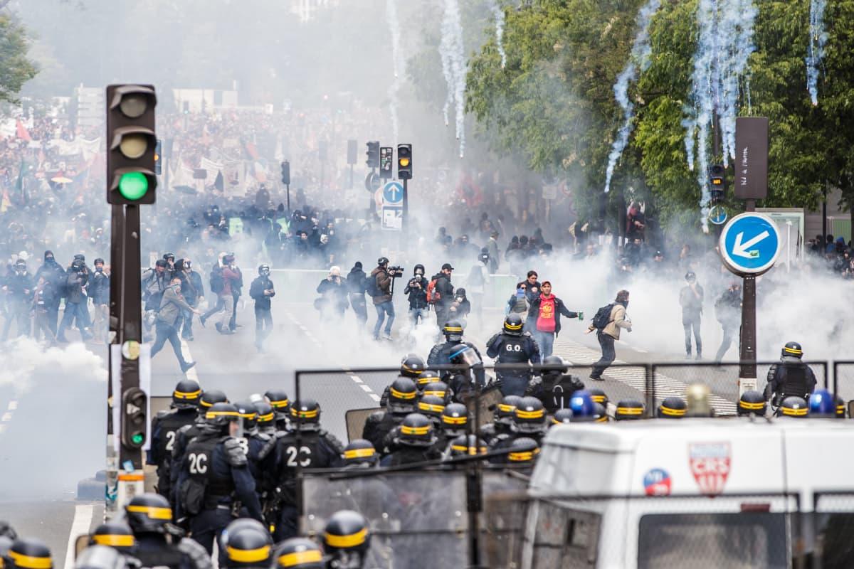 Kuvassa leveä katu, etualalla poliiseja, joita kohti vappumarssi kulkee. Marssijoiden edessä on mustiin pukeutuneita mellakoitsijoita. Kuvassa kyynelkaasua ja savupommeja .