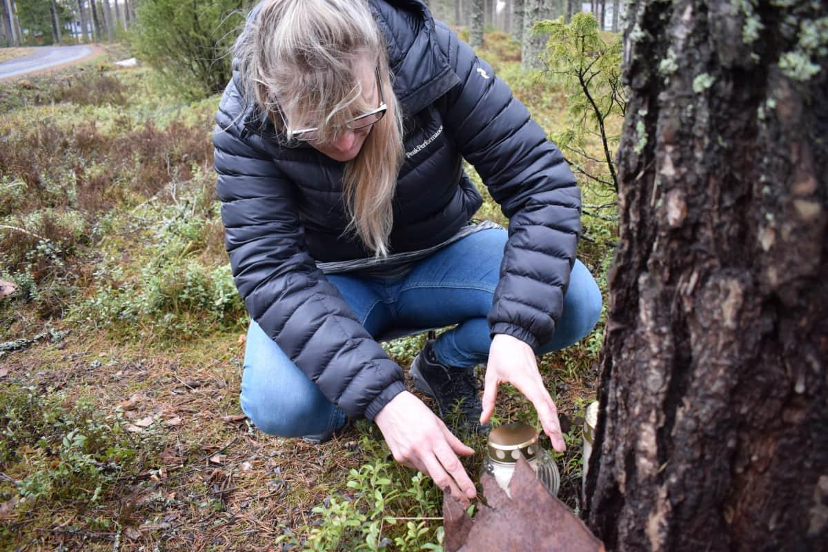 Anna-Leena Suni sytyttää hautakynttilää.
