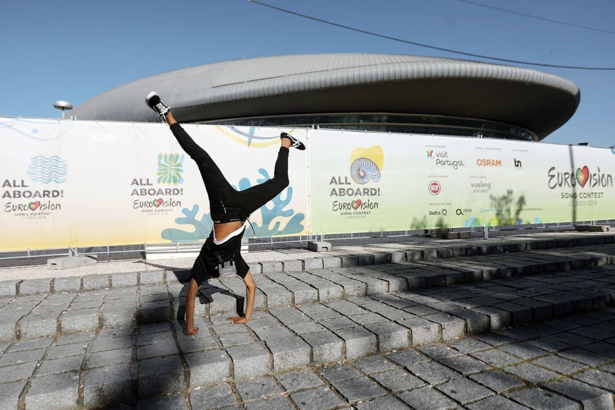 Mies tanssii euroviisujen pitopaikan edustalla Lissabonissa.