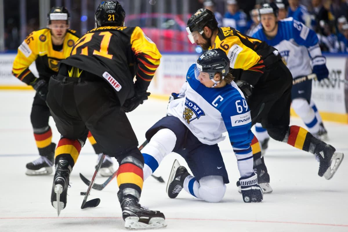 Mikael Granlund kaatuu saksalaispelaajien keskellä MM-kisoissa.