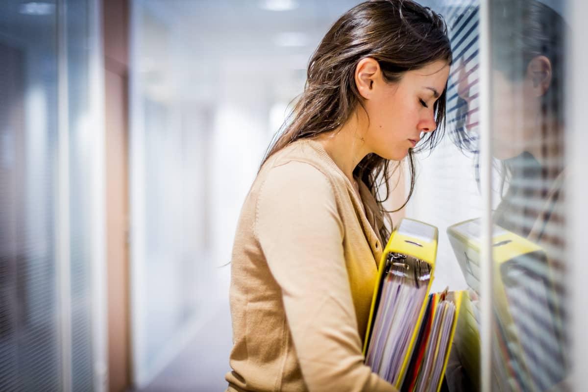 Nainen nojaa päätää toimiston lasiseinään mapit kädessä ja vaikuttaa hyvin uupuneelta. Uupumukseen voi liittyä se, ettei osaa kieltäytyä asioista, vaan suorittaa liikaa.