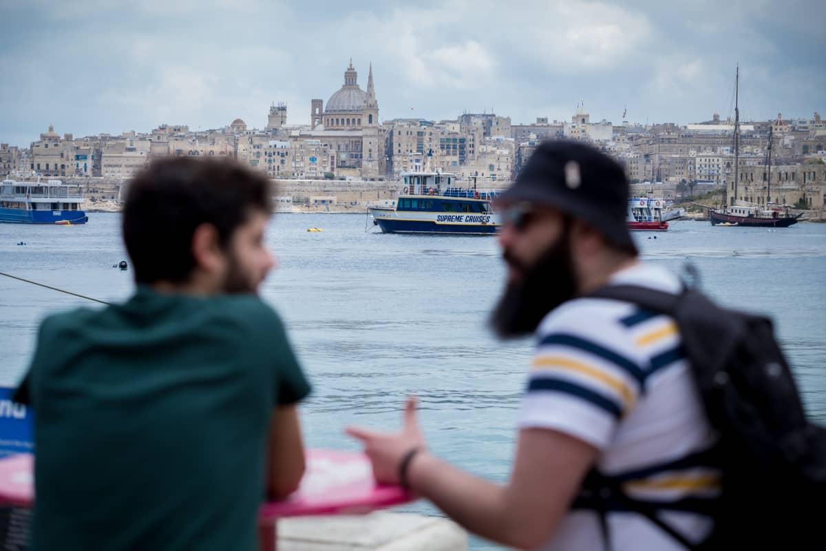 Nuoria etualalla, taustalla Vallettan kaupungin siluetti