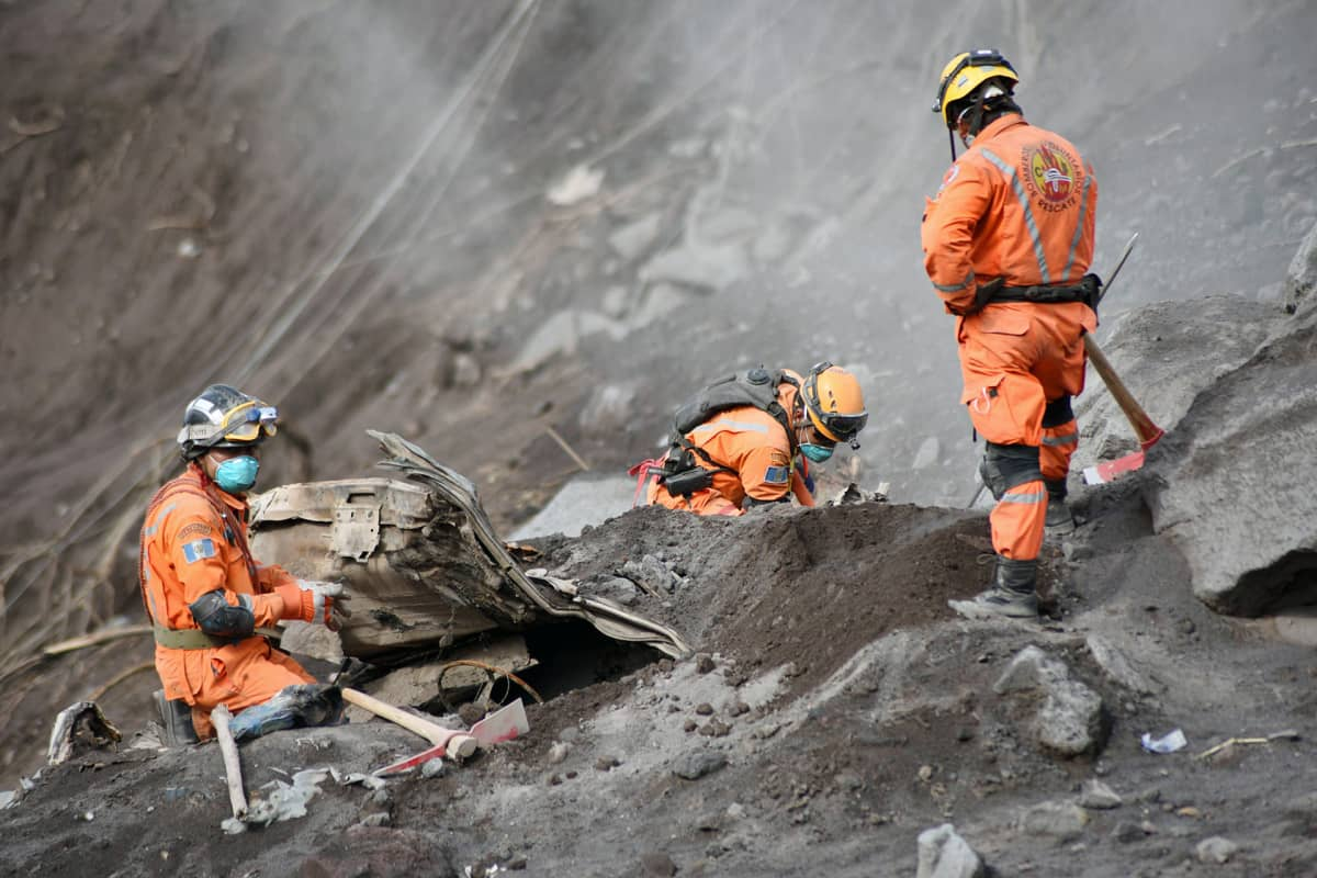 Vapaaehtoiset palomiehet etsivät tulivuorenpurkauksen uhreja Alotenangossa.