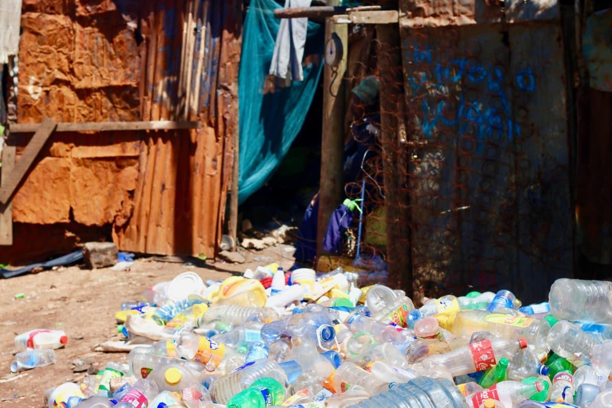 Jeremiah Mdongo kierrättää muovipulloja työkseen. Hän istuu hökkelinsä ulkopuolella Kiberan slummin laidalla Nairobissa.