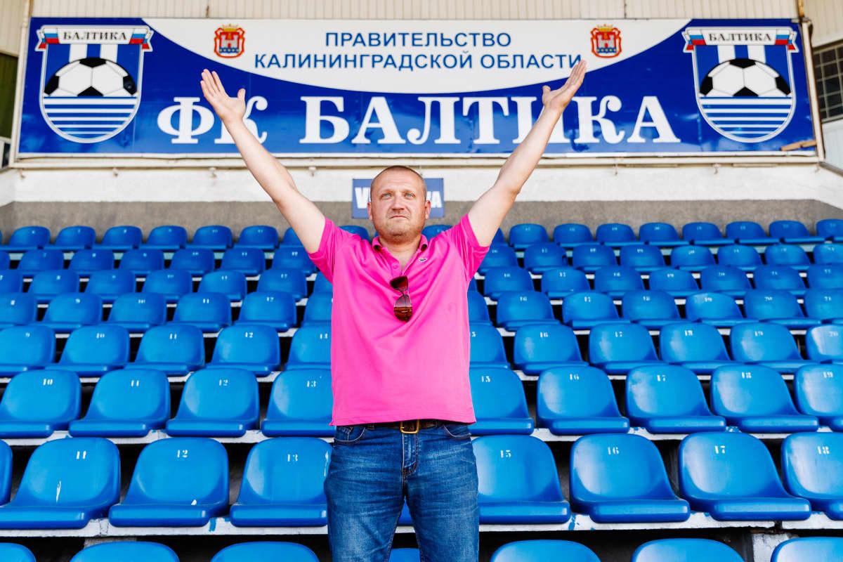 Vaaleanpunaiseen Lacosten pikee-paitaan ja farkkuihin sonnustautunut keski-ikäinen mies seisoo stadionin katsomossa kädet ylös nostettuina. Katsoman seinässä lukee joukkueen nimi: Baltika.