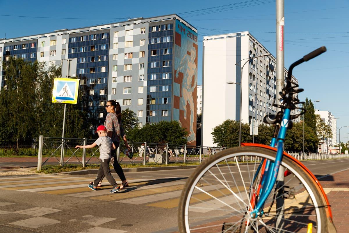 Kuvan etualalle on parkkeerattu polkupyörä. Nainen ja poika ylittävät suojatietä. Taustalla on rykelmä kerrostaloja. Yhden talon seinässä on jalkapallon MM-kisoja mainostava suuri seinämaalaus.