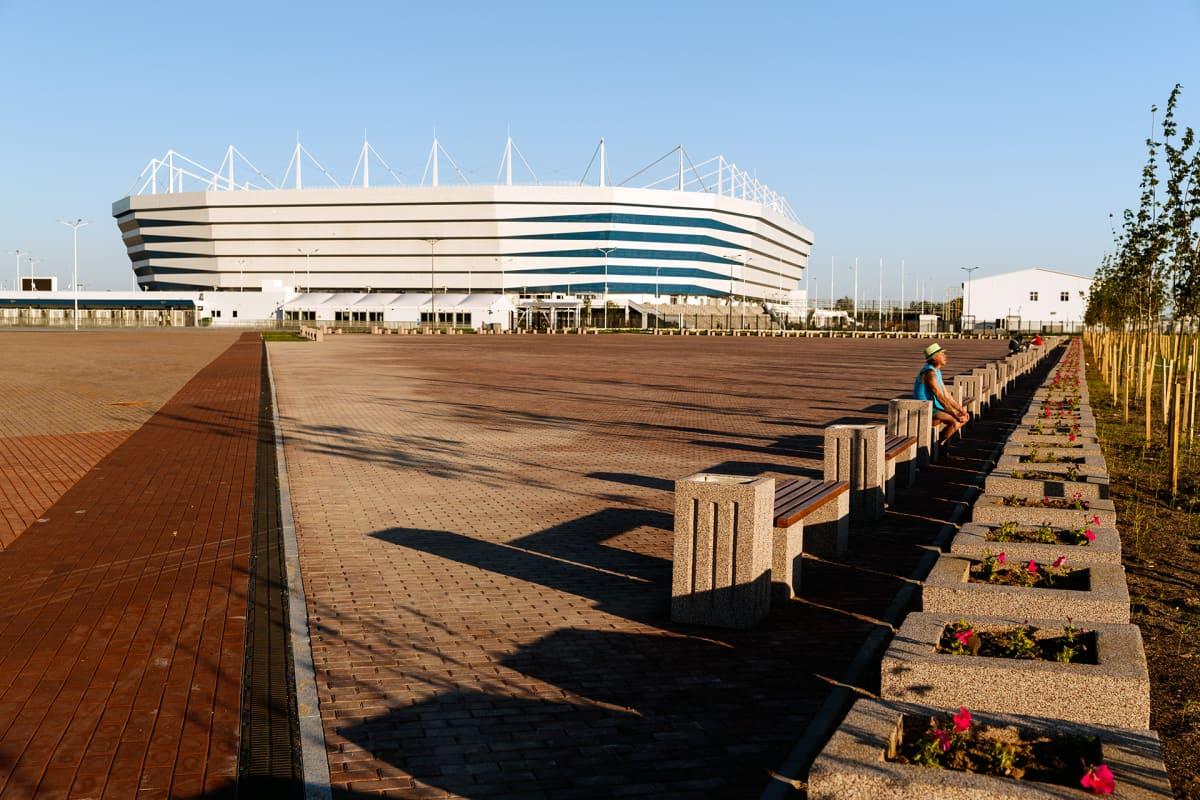 Kaliningradin uusi stadion ilta-auringossa. Etualalla on penkkirivistö, jossa istuu mies.
