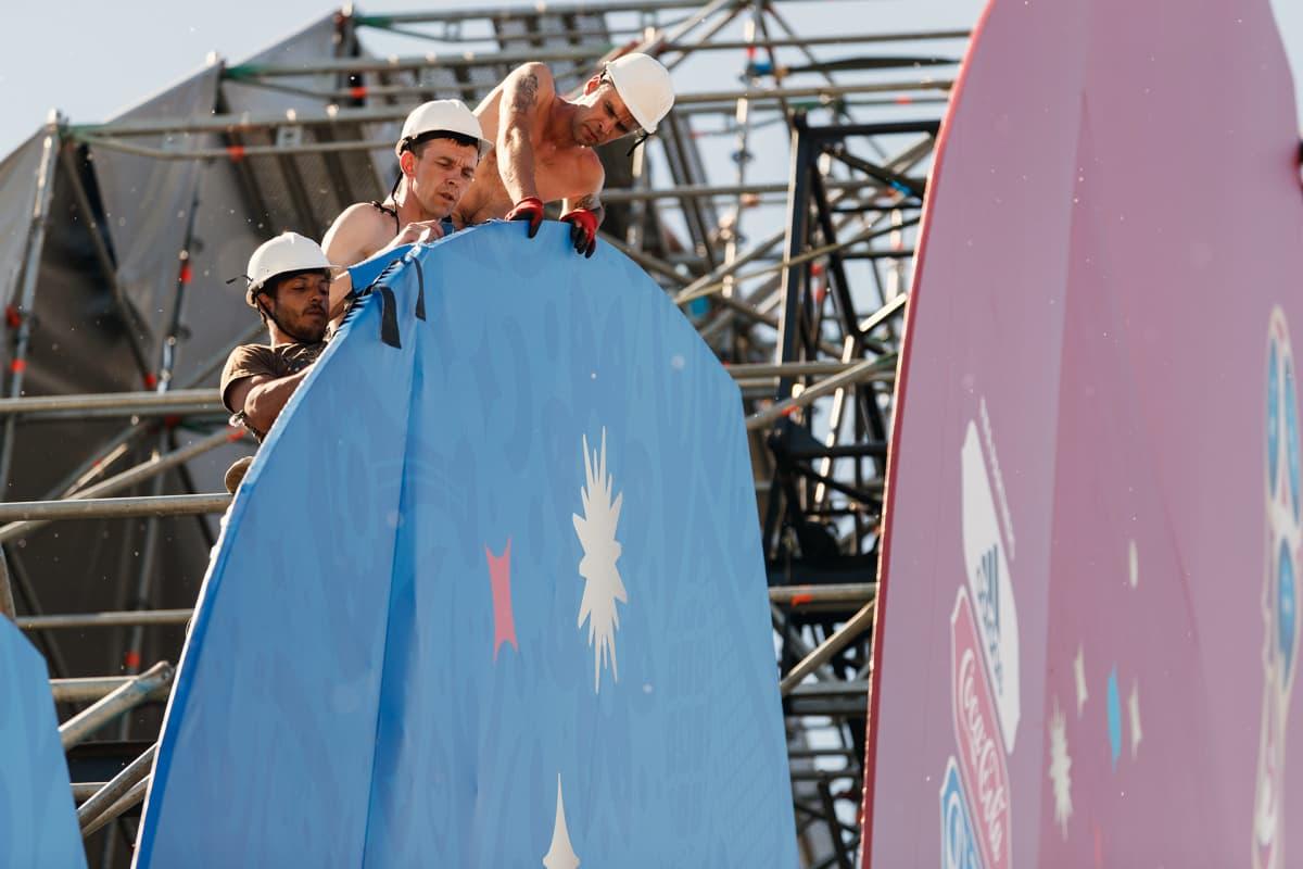 Kolme työmiestä asettelee sinistä kangasta kehikkoon näyttämöllä.