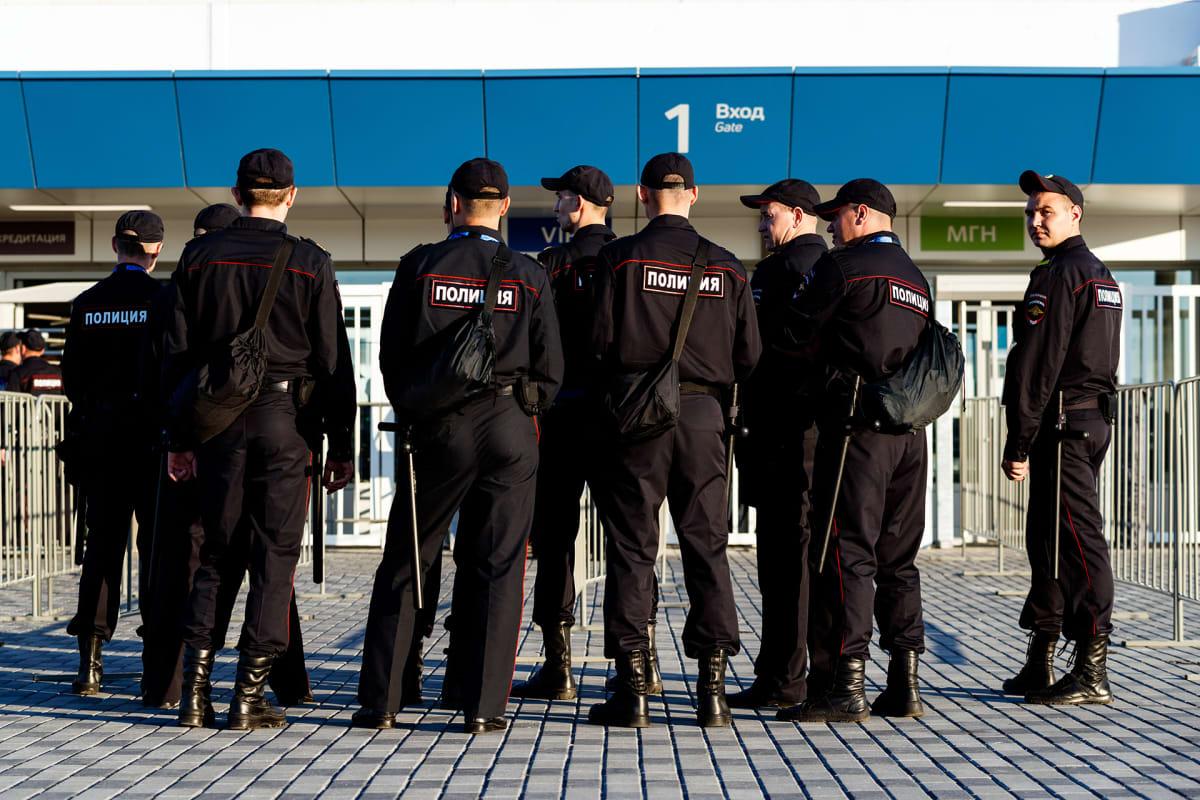 Joukko poliiseja seisoo stadionin porttien tuntumassa. Heillä on mustat univormut ja lippalakit. Vöistä riippuu pitkiä pamppuja.