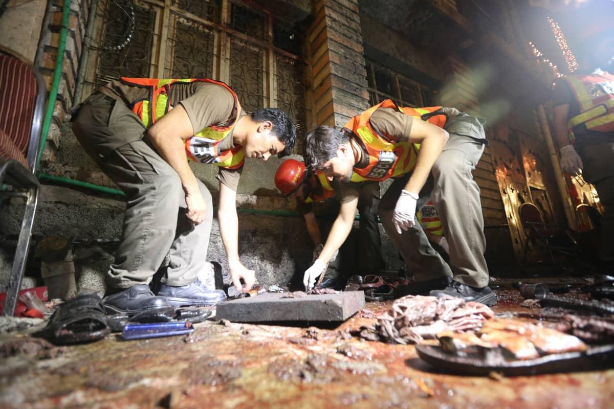 Pelastustyöntekijät tarkastavat iskun kohteena ollutta vaalitilaisuuden pitopaikkaa Peshawarissa.