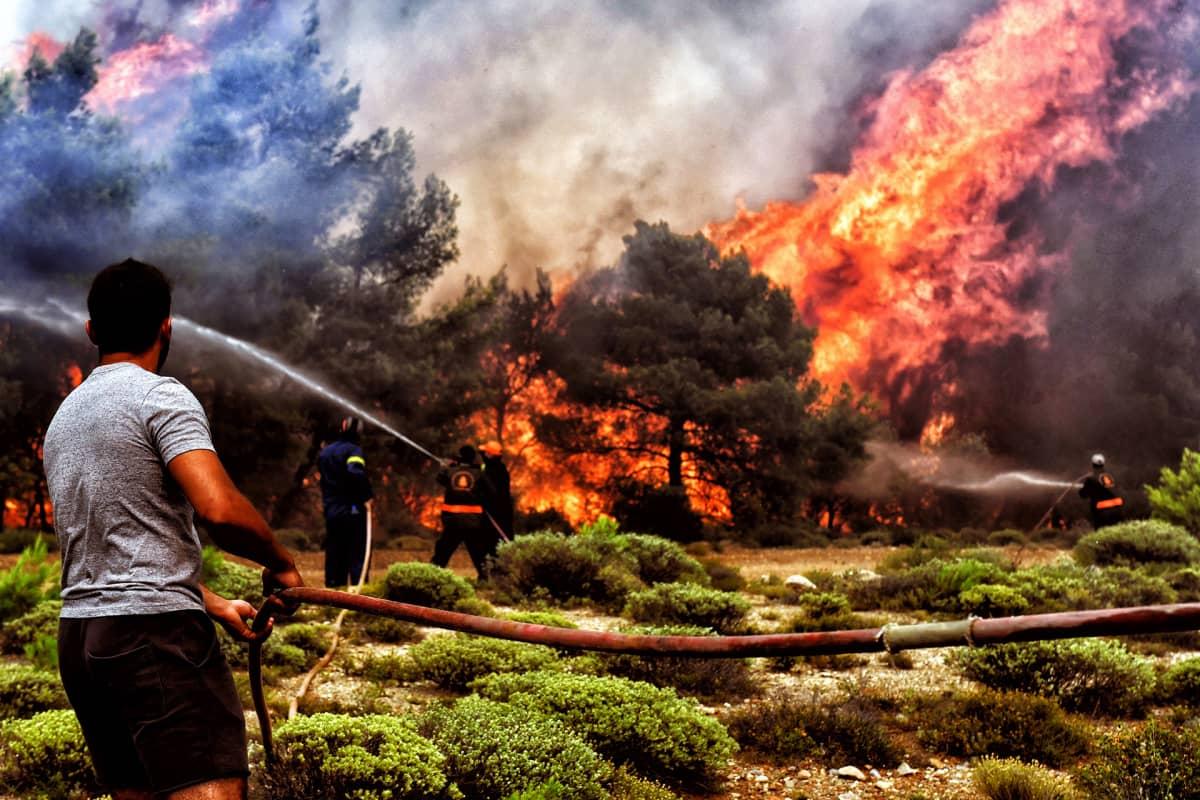 Palomiehet ja vapaaehtoiset yrittävät hillitä maastopaloa Loutrakin lähistöllä Kreikassa.