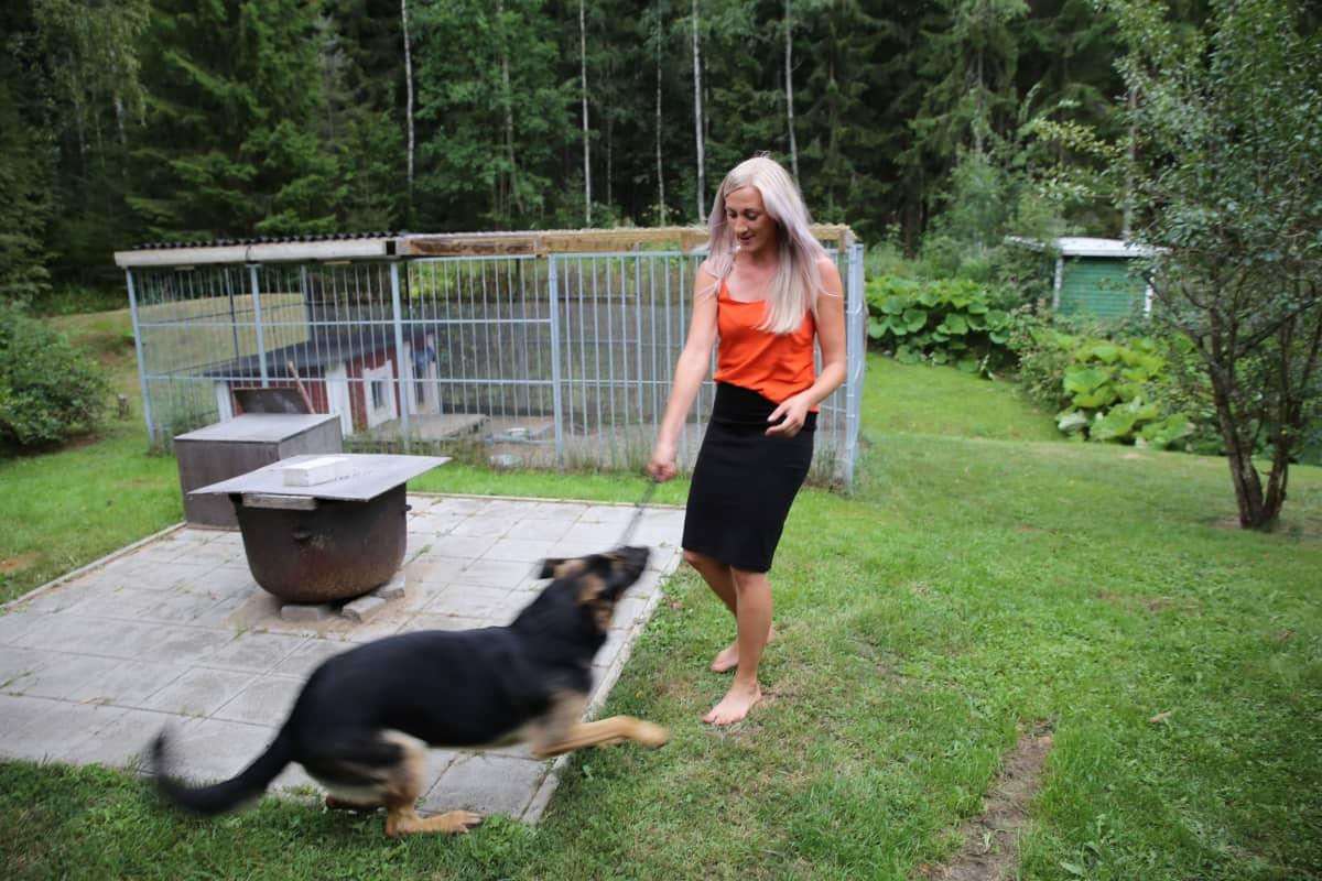 Laura Salmela leikkii koiransa kanssa.