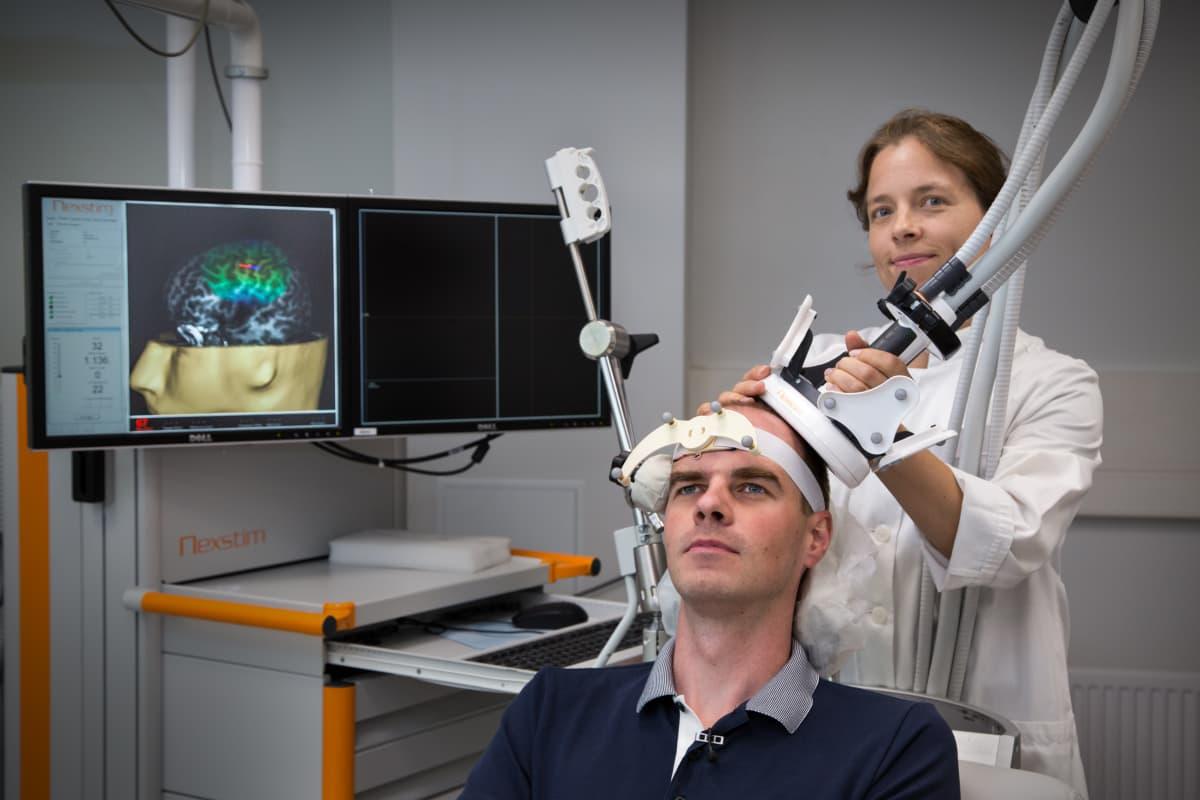 Kliinisen neurofysiologian erikoislääkäri Selja Vaalto esittelee yhdessä Aalto-yliopiston tutkija Jaakko Niemisen kanssa TMS laitetta.