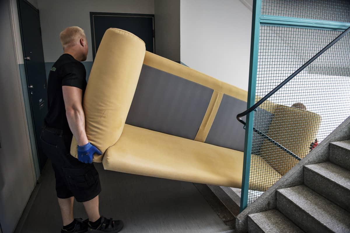 Muuttomiehet kantavat sohvaa rappukäytävässä.