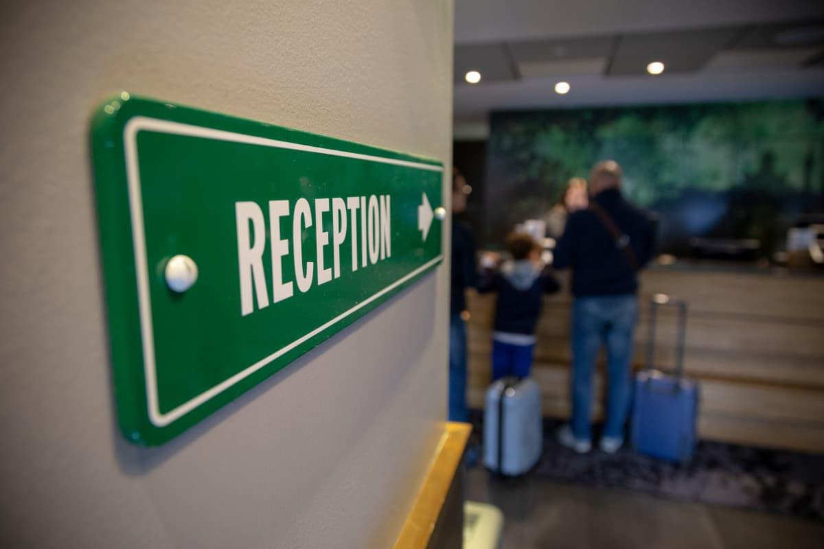 Kuva hotellivastaanoton vihreästä kyltistä, jossa lukee reception.