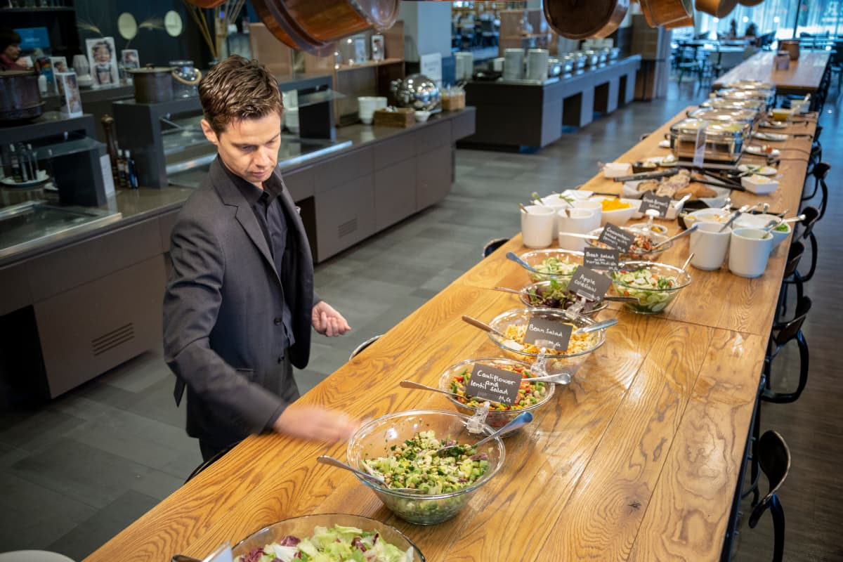 Ravintolan työntekijä järjestelee lounaspöytää.