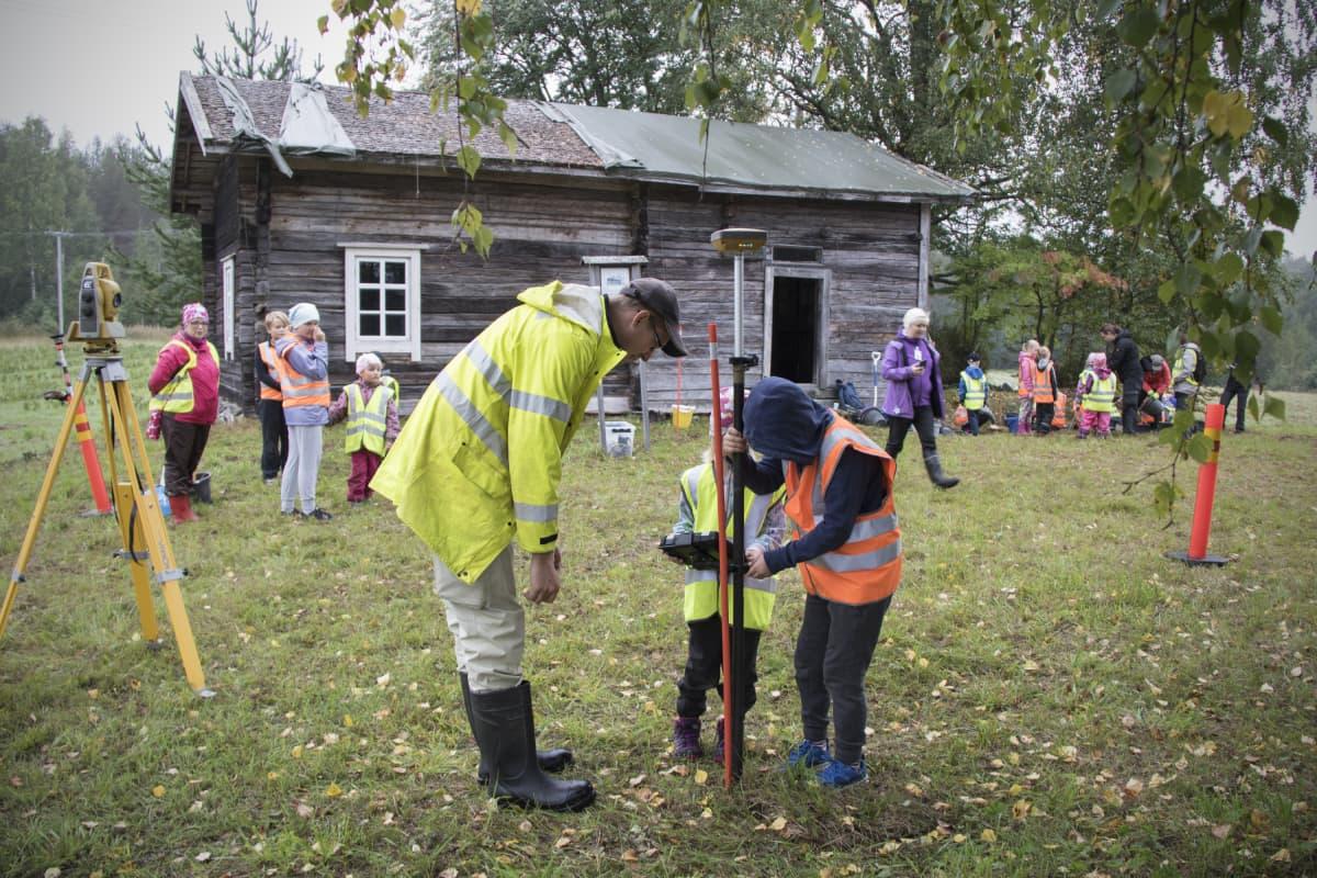 Koululaiset mittaavat vanhan talon pihapiiriä Kontiolahdella.