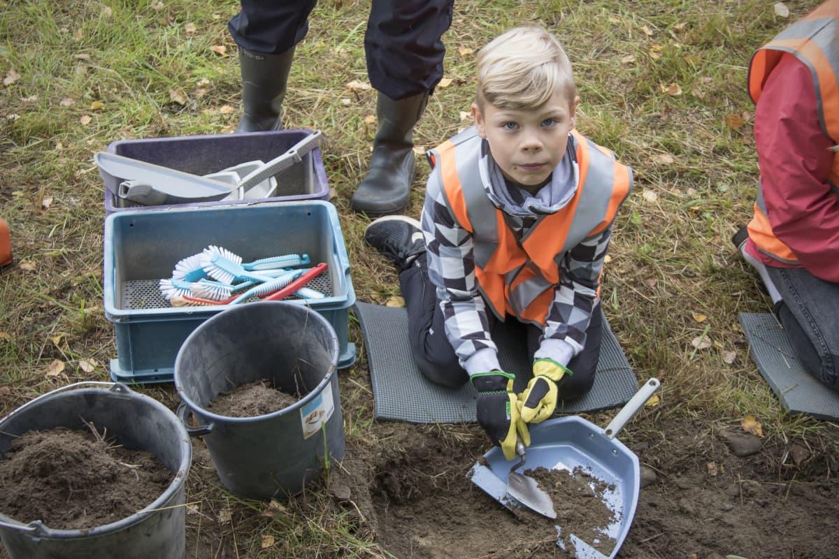 Peetu Vannas etsii maaperästä esineitä lapioimalla multaa rikkalapioon.