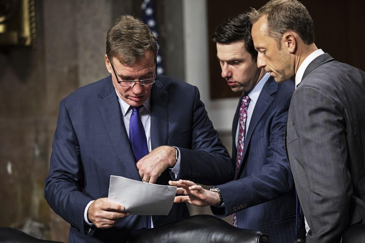 Senaattori Mark Warner (vas.) näyttää paperia Twitterin johtajalle Jack Dorseylle ja Facebookin johtajalle Sheryl Sandbergille.