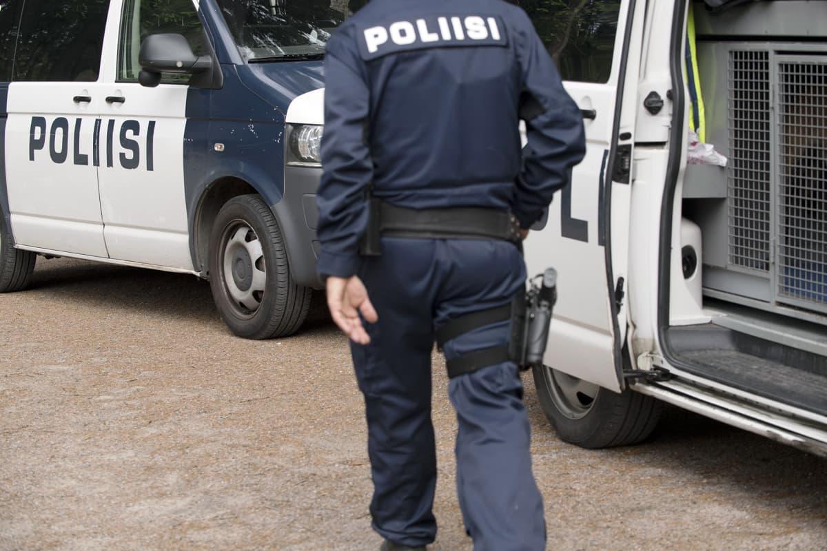 Poliisi poliisiauton edustalla.