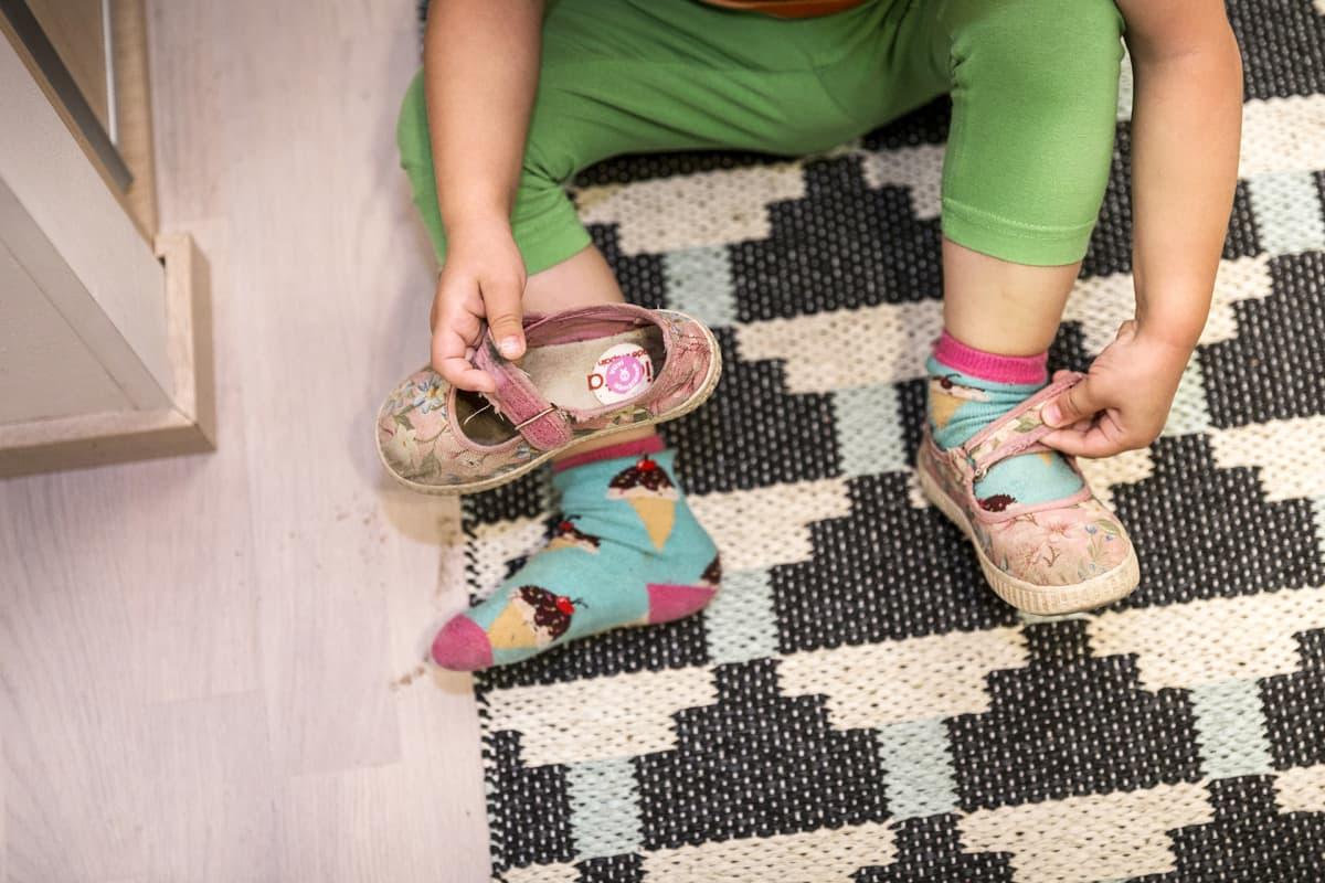 lapsi laittaa kenkiä jalkaan