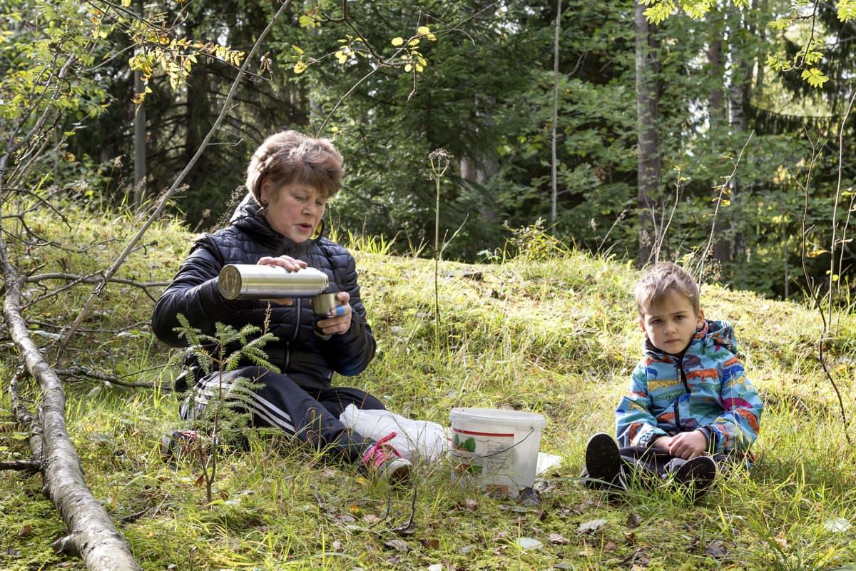 Marjaana Backman ja Arvi Henriksson kahvittelevat metsässä.