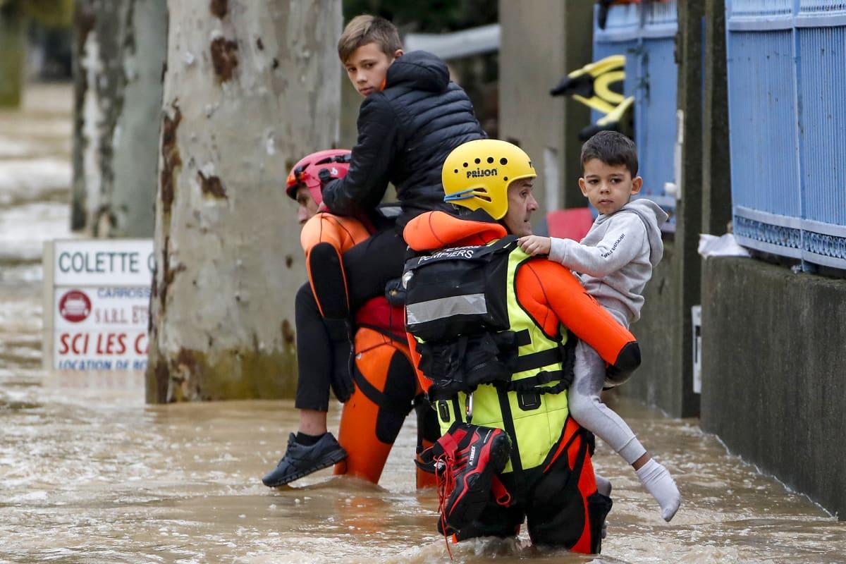pelastajat kahlaavat kantaen kahta lasta